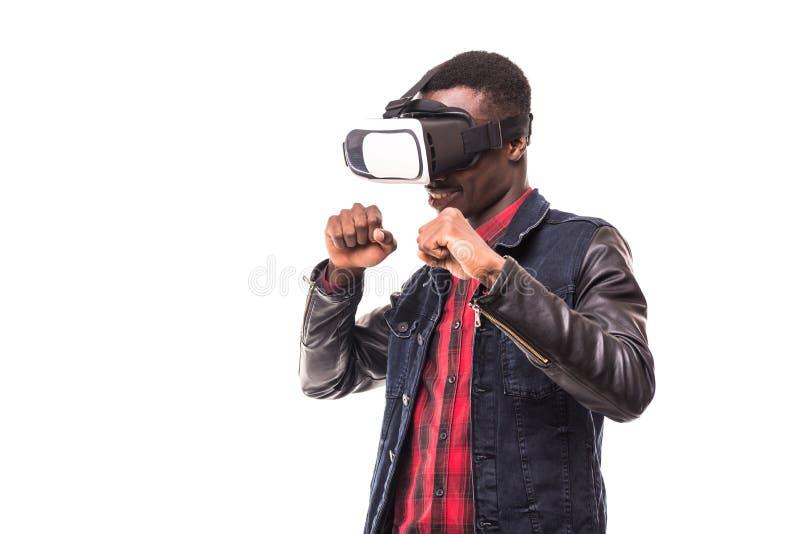 戴正式衣服和虚拟现实耳机或3d眼镜的非洲人,打电子游戏,打手势用他的手和catchi 免版税库存图片