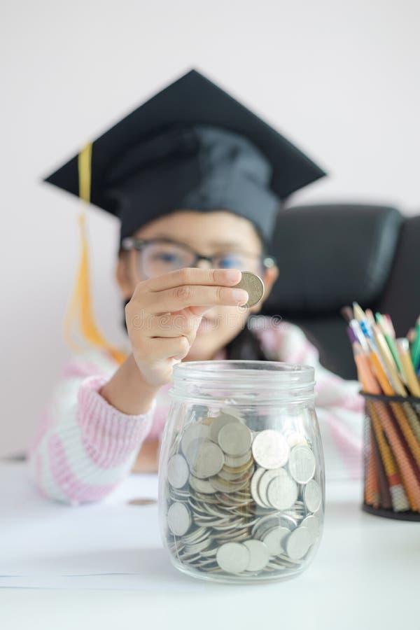 戴毕业生帽子的小亚裔女孩放硬币入清楚的玻璃瓶子存钱罐和微笑充满幸福节约金钱的 免版税库存图片