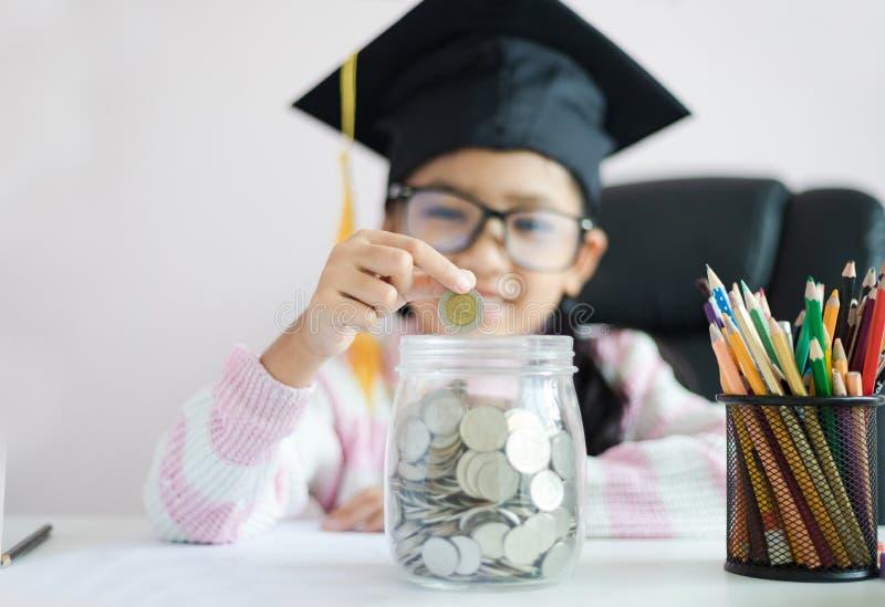 戴毕业生帽子的小亚裔女孩放硬币入清楚的玻璃瓶子存钱罐和微笑充满幸福节约金钱的 免版税库存照片