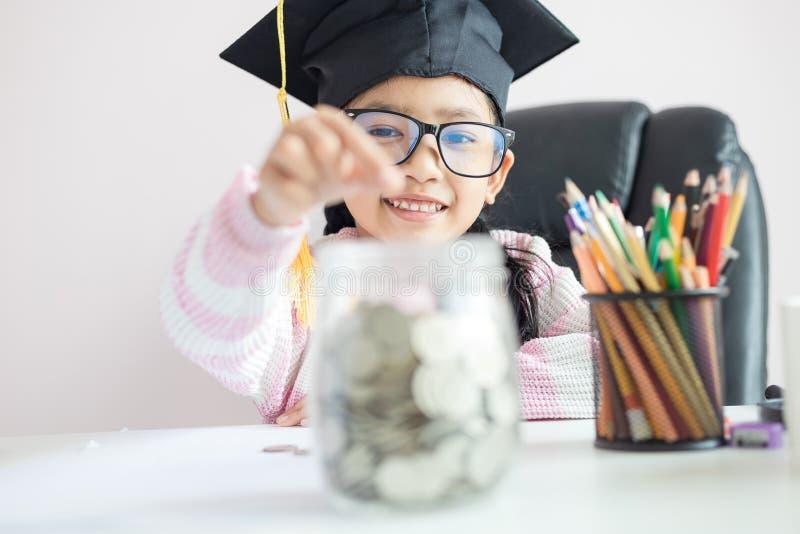 戴毕业生帽子的小亚裔女孩放硬币入清楚的玻璃瓶子存钱罐和微笑充满幸福节约金钱的 免版税图库摄影