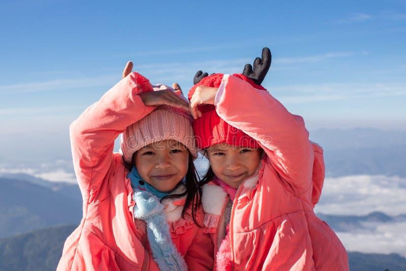 戴毛线衣和温暖的帽子的两个亚裔儿童女孩做心脏与爱一起在美丽的薄雾和山 免版税库存照片