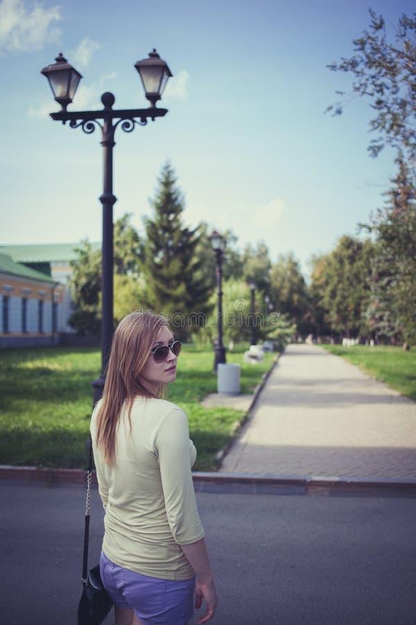 戴流动的头发在短的短裤和眼镜的美女在一条沥青路线的背景有灯笼的 库存照片