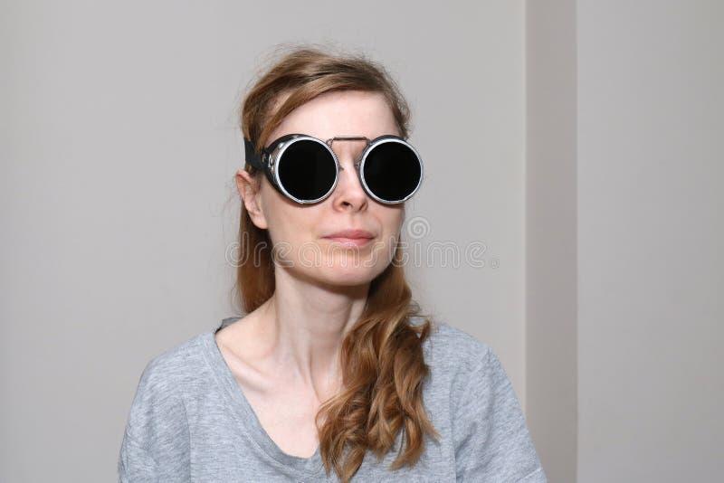 戴焊接的眼镜的年轻女人 库存图片