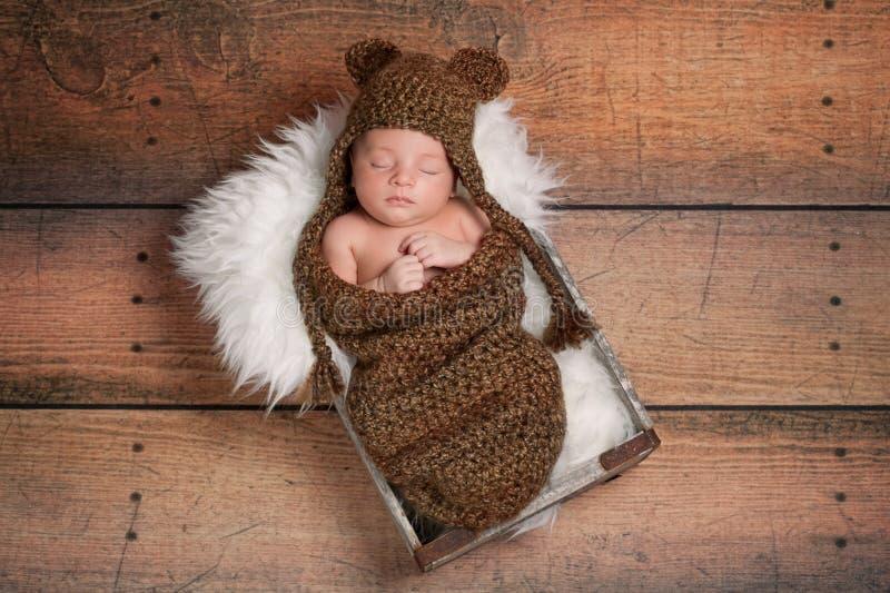 戴熊帽子的休眠的新出生的男婴 库存图片