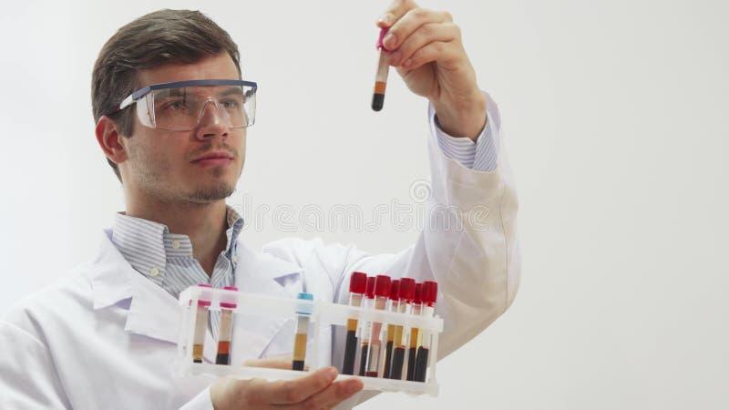 戴特别实验室眼镜的医生审查有血液的试管 图库摄影
