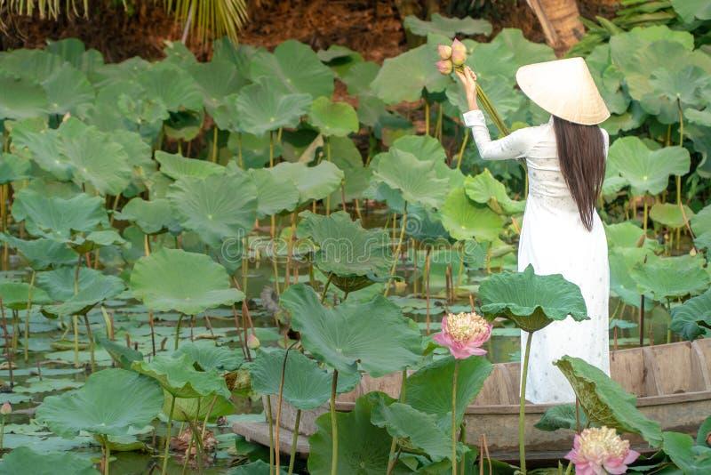 戴白色白色传统越南礼服Ao Wai和越南农夫的帽子和站立在木小船的美丽的亚洲妇女 库存照片