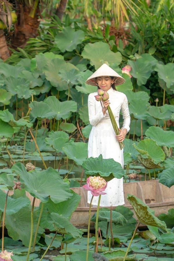 戴白色白色传统越南礼服Ao Wai和越南农夫的帽子和站立在木小船的美丽的亚洲妇女 免版税库存照片