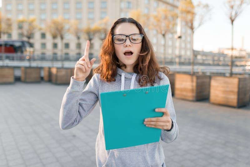 戴看剪贴板和显示注意,想法,尤里卡,金黄小时的眼镜的聪明的女孩食指 图库摄影