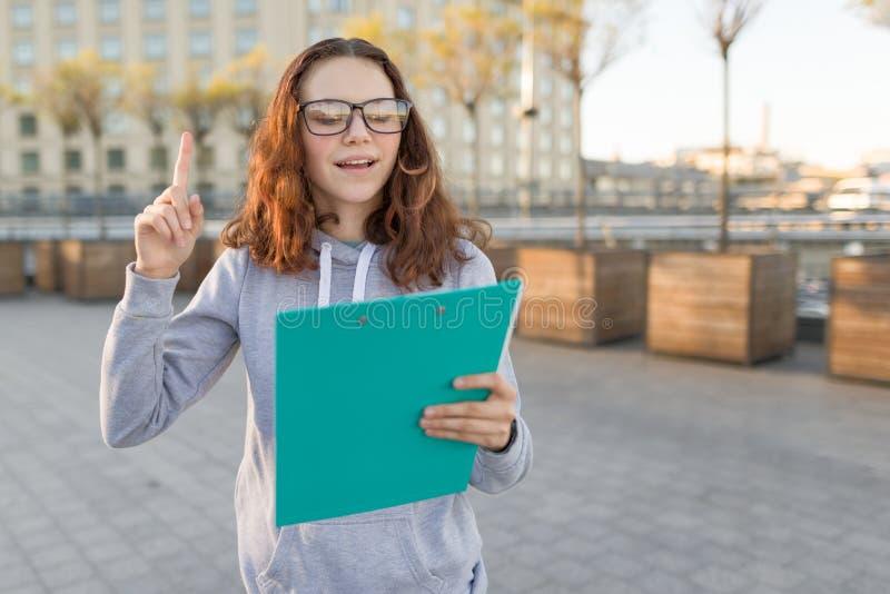 戴看剪贴板和显示食指的眼镜的聪明的女孩  免版税库存图片