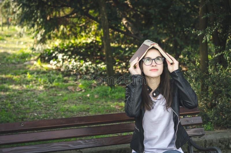 戴眼睛眼镜的年轻美丽的学校或女大学生坐长凳在读的公园书休假和 库存照片