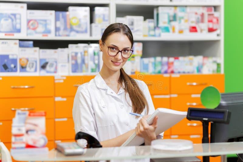 戴眼镜的一个年轻的宜人的深色头发的女孩,穿戴在医疗总体,在笔记本写笔记在现金 库存图片