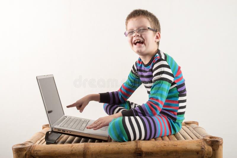 戴眼镜的一个白种人男孩设法与计算机和互联网一起使用 人得到生动的情感 免版税库存图片