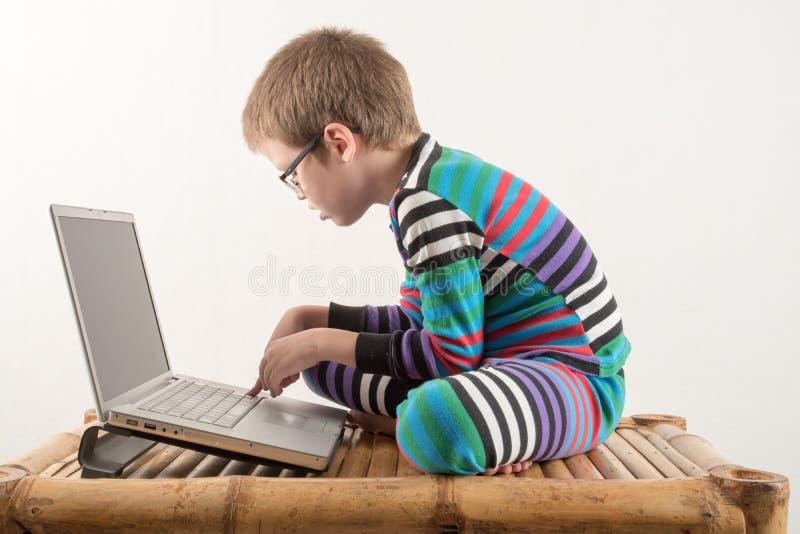 戴眼镜的一个白种人男孩设法与计算机和互联网一起使用 人得到生动的情感 库存图片