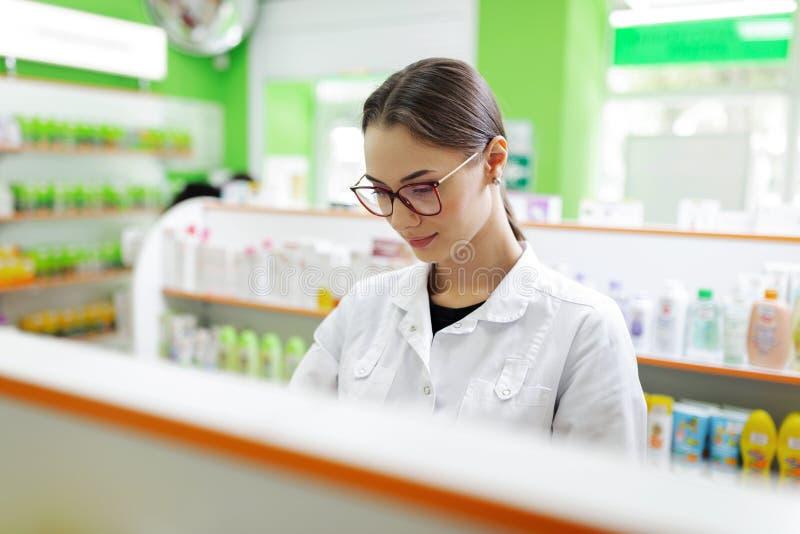 戴眼镜的一个美丽的亭亭玉立的棕色毛发的女孩,穿实验室外套,专心地看在一家现代药房的架子 图库摄影
