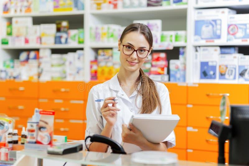 戴眼镜的一个美丽的稀薄的深色头发的女孩,穿戴在实验室外套,在笔记本写笔记在收银处和 库存照片