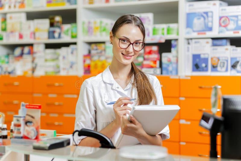 戴眼镜的一个美丽的稀薄的深色头发的女孩,穿戴在实验室外套,在笔记本写笔记在a的收银处 免版税库存图片