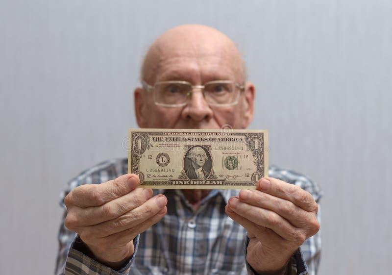 戴眼镜的一个老秃头人拿着在他前面的一张钞票-一美元 免版税库存照片