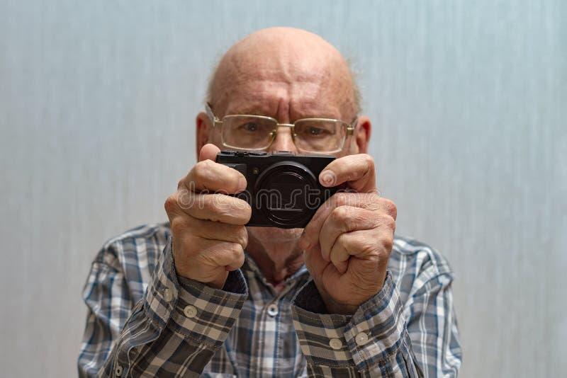 戴眼镜的一个老秃头人看在照相机的英尺长度 ??Spac 免版税库存图片
