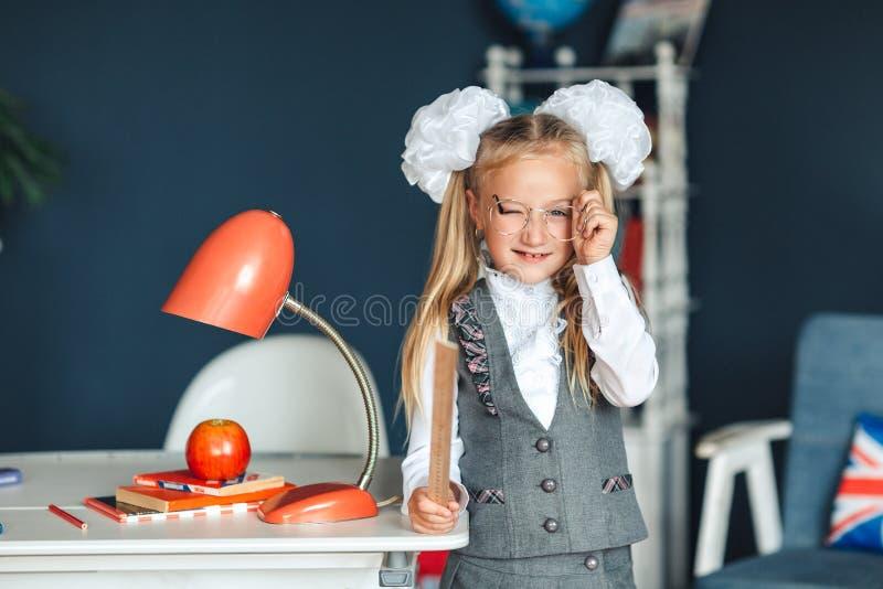 戴眼镜的一位嬉戏的逗人喜爱的矮小的女小学生和她的手闪光的一个统治者 她获得乐趣,当依靠桌时 她的头发栓了 免版税图库摄影