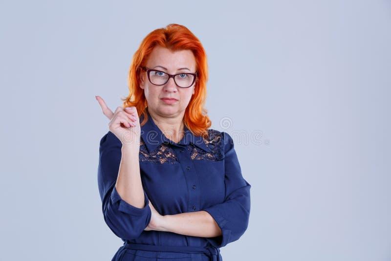 戴眼镜的一名妇女握她的食指反对特写镜头灰色背景 图库摄影