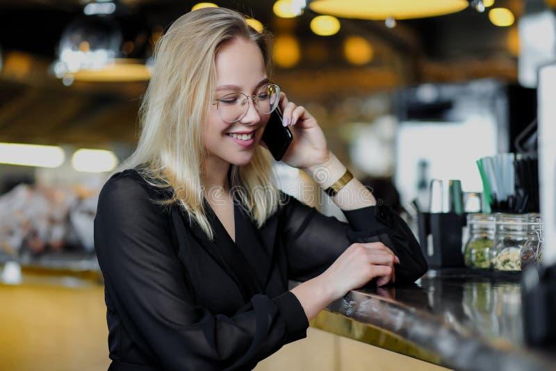 戴眼镜的一名年轻美丽的白肤金发的妇女坐在黄色内部的酒吧 喝与秸杆的酒精鸡尾酒 免版税库存照片