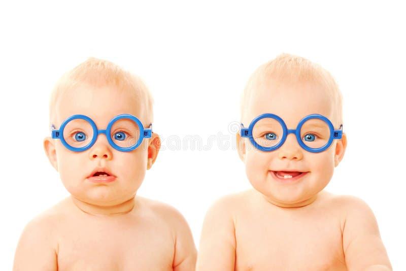 戴眼镜的二个孪生男婴。 免版税库存图片
