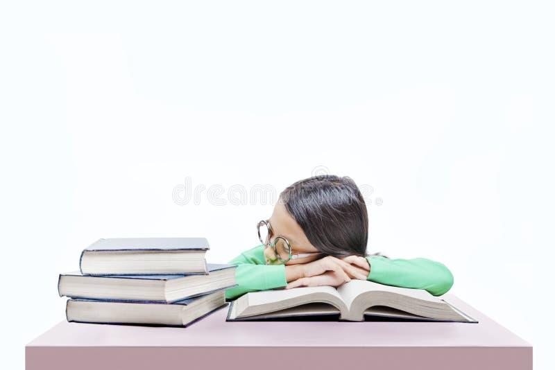 戴眼镜的亚裔逗人喜爱的女孩睡着在书桌上的书 免版税库存照片