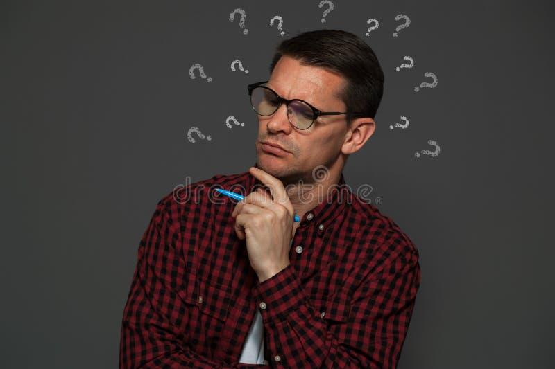 戴眼镜的体贴的人和笔在他的手上 免版税库存图片