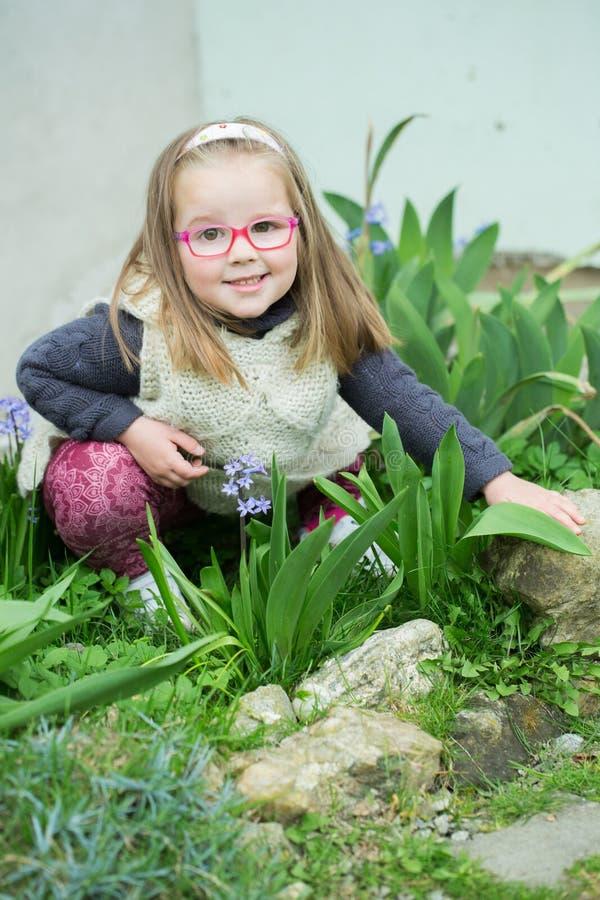 戴眼镜的儿童女孩在庭院里 免版税库存照片