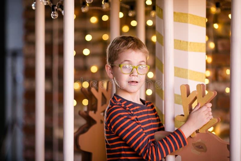 戴眼镜的好白肤金发的男孩在有木鹿和明亮的光的新年转盘 库存图片