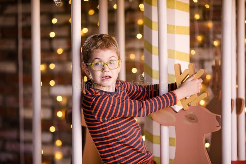 戴眼镜的好白肤金发的男孩在有木鹿和明亮的光的新年转盘 免版税库存照片