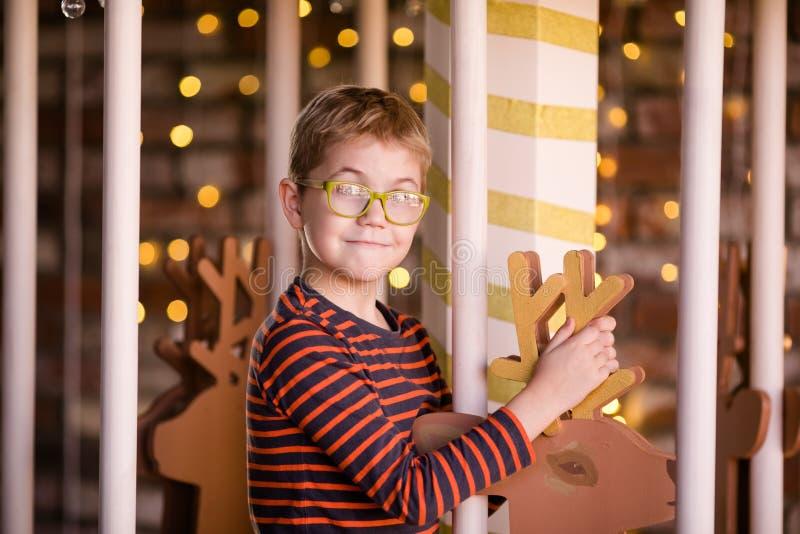 戴眼镜的好白肤金发的男孩在有木鹿和明亮的光的新年转盘 库存照片