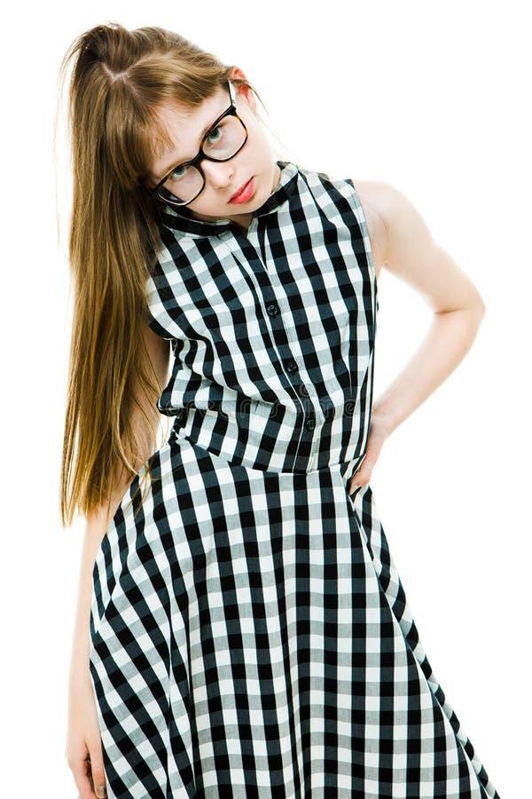 戴眼镜的学生女孩在黑方格的礼服 免版税库存照片