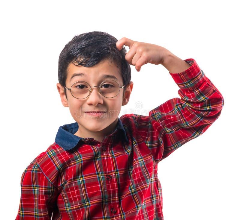 戴眼镜的小男孩抓他的头 免版税库存图片