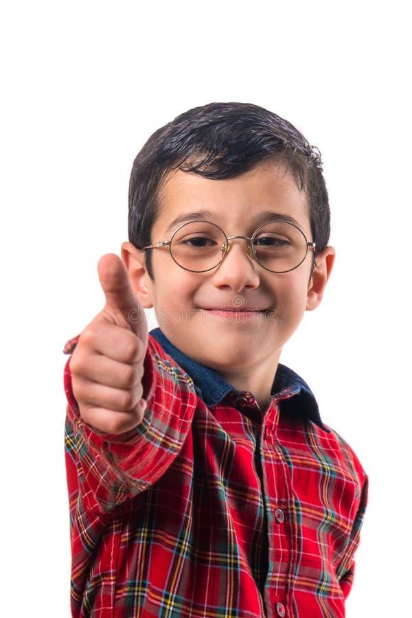 戴眼镜的小男孩显示大手指  免版税库存照片
