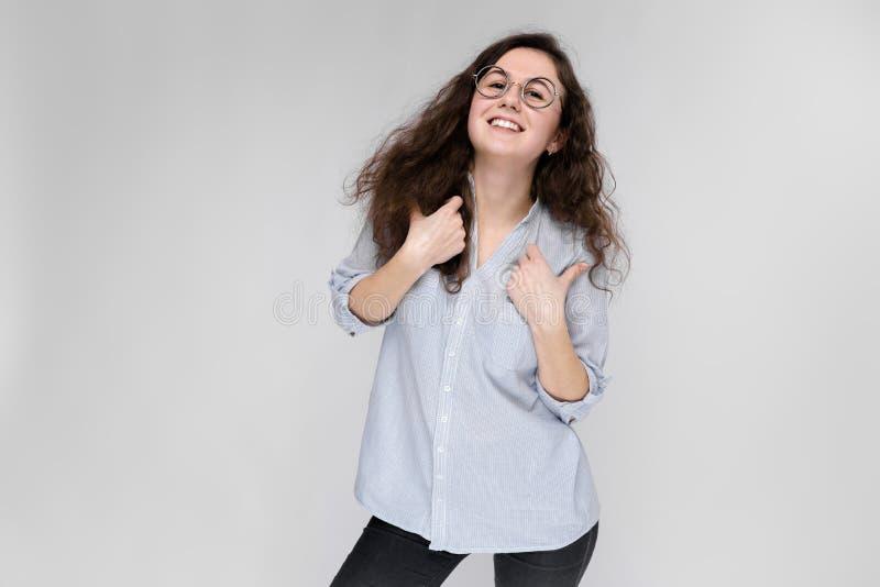戴眼镜的年轻深色的女孩 女孩显示类标志 免版税库存图片