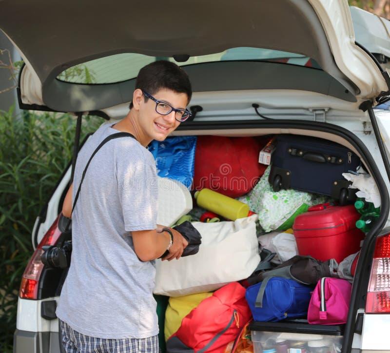 戴眼镜的年轻男孩在汽车的行李投入手提箱 免版税库存照片