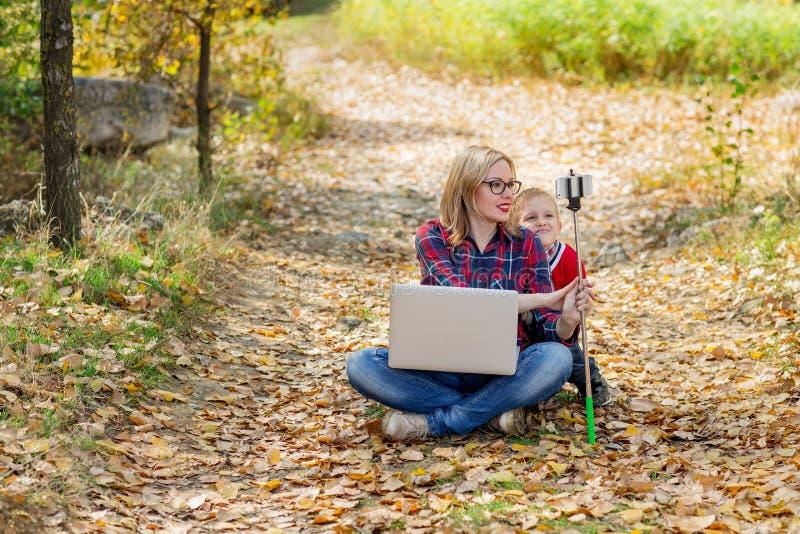 戴眼镜的年轻美丽的妈咪拿着一台膝上型计算机在她的膝部和在显示她的孩子某事的自棍子的手上  免版税库存图片