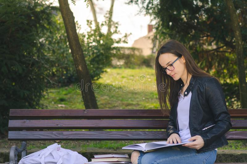 戴眼镜的年轻美丽的学校或女大学生坐长凳在公园读书和研究检查的, educati的 免版税库存照片