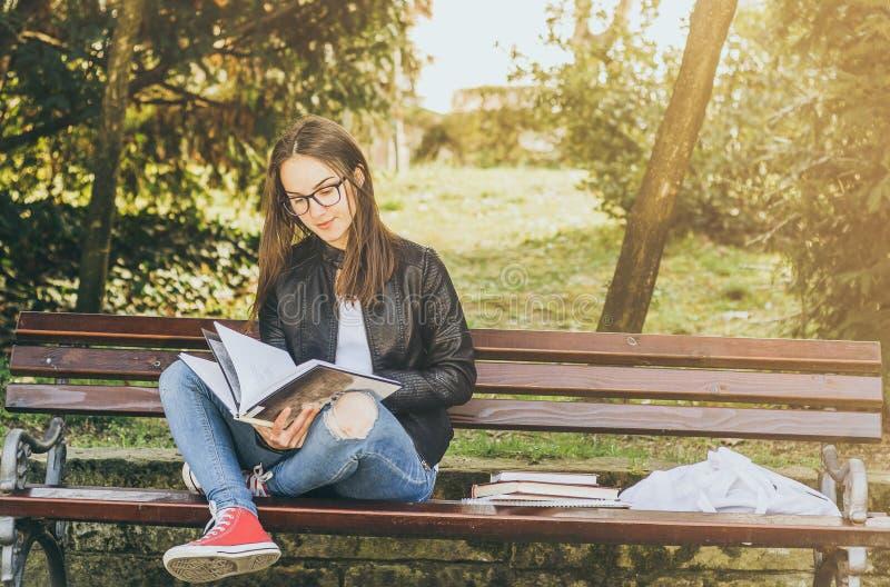 戴眼镜的年轻美丽的学校或女大学生坐长凳在公园读书和研究检查的 免版税库存图片