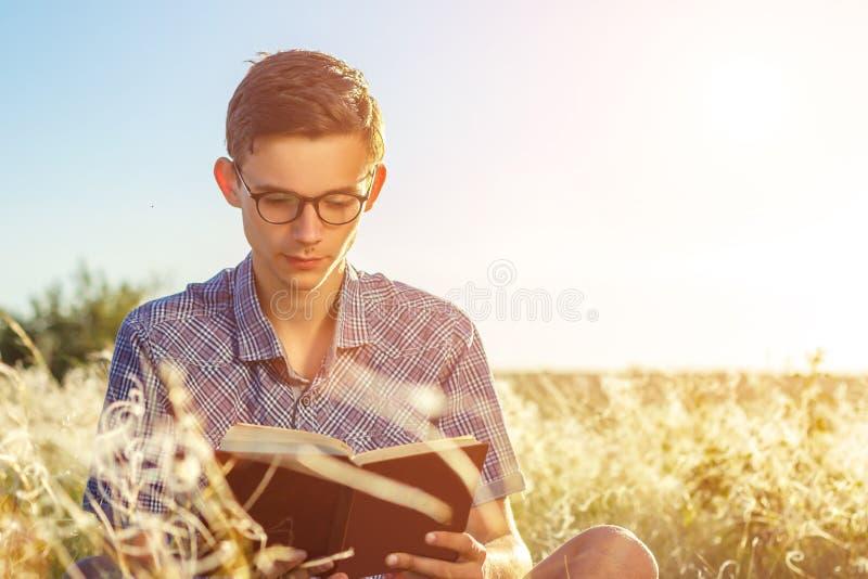 戴眼镜的年轻英俊的人读与玻璃的一本书在一个晴天 图库摄影