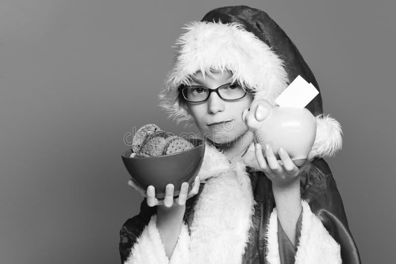 戴眼镜的年轻逗人喜爱的圣诞老人男孩在拿着桃红色贪心猪银行的红色毛线衣和新年圣诞节帽子和 免版税库存图片
