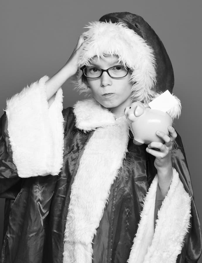 戴眼镜的年轻逗人喜爱的圣诞老人项目男孩在拿着桃红色贪心猪银行与的红色毛线衣和新年圣诞节帽子 免版税库存照片