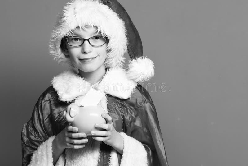戴眼镜的年轻逗人喜爱的圣诞老人项目男孩在xmas拿着红色的毛线衣和新年圣诞节帽子桃红色贪心猪银行 库存图片