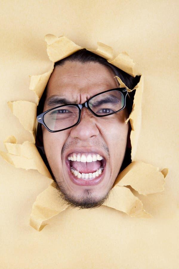 戴眼镜的恼怒的年轻人 免版税库存图片