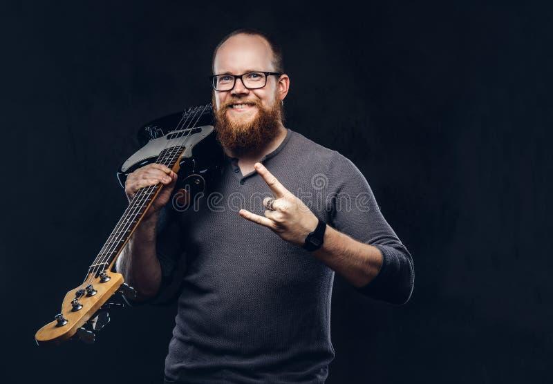 戴眼镜的愉快的红头发人有胡子的男性音乐家穿戴在一件灰色T恤杉拿着电吉他和展示岩石和 免版税库存图片
