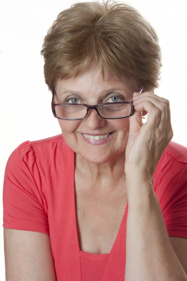 戴眼镜的愉快的高级妇女 免版税库存照片