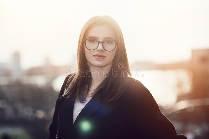 戴眼镜的美丽的年轻成人女商人在日落时间 免版税库存照片