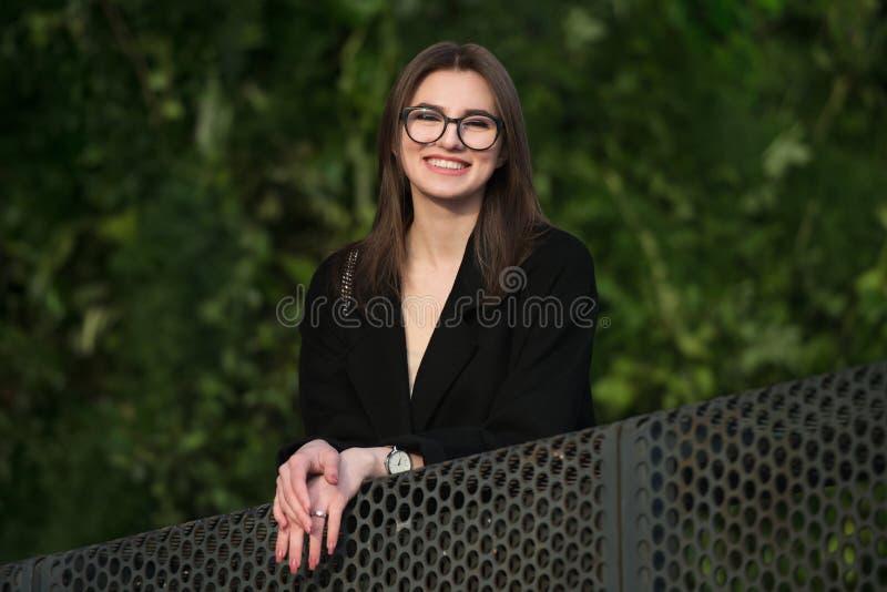 戴眼镜的美丽的年轻成人微笑的妇女微笑户外在公园的 图库摄影
