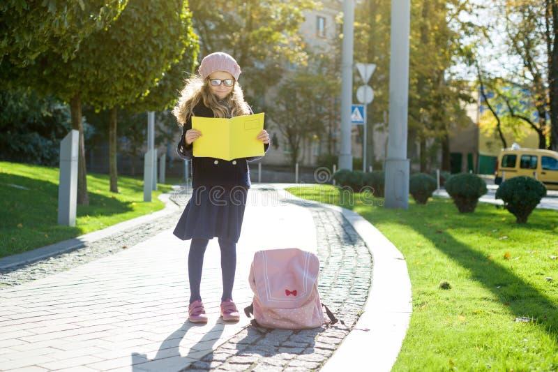 戴眼镜的逗人喜爱的小女孩,外套,法国贝雷帽在笔记本看 免版税库存照片